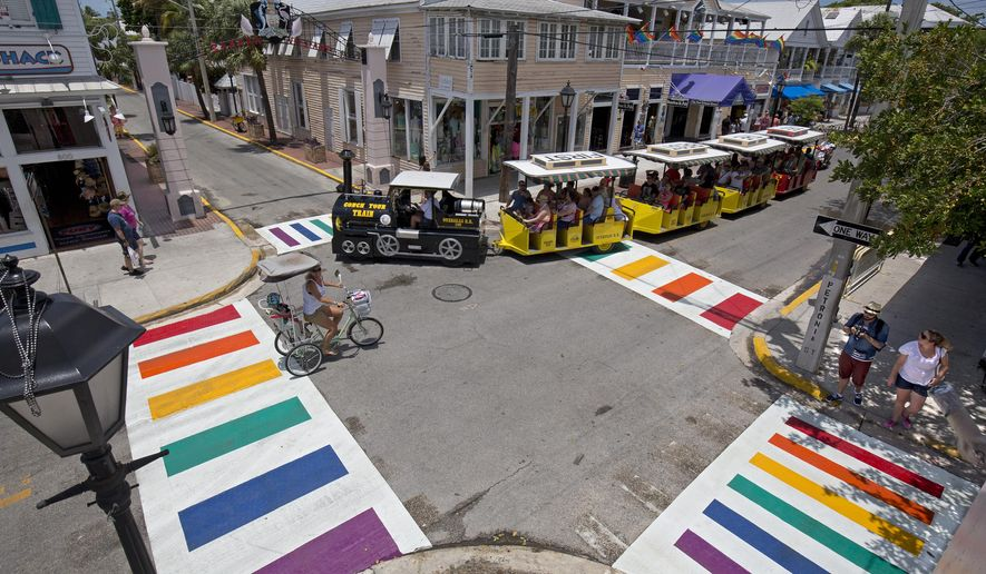 In this photo provided by the Florida Keys News Bureau, a Conch Tour Train turns at Duval and Petronia streets Thursday, May 28, 2015, in Key West, Fla., just after city workers installed four rainbow crosswalks. The crosswalks feature bands of all six colors of the rainbow flag, an internationally recognized symbol of gay and lesbian unity. The crosswalks are composed of pre-formed thermoplastic color blocks alternating with white stripes, heat-treated to become a permanent part of the pavement. (Rob O'Neal/Florida Keys News Bureau via AP)