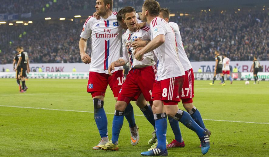 Hamburg's  players celebrate after Ivo Ilicevic scored the first goal of his team  during the German first division Bundesliga first leg relegation soccer match between Hamburger SV and Karlsruher SC in Hamburg, Germany, Thursday, May 28, 2015. (AP Photo/Joerg Sarbach)