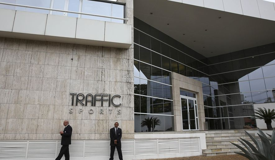 Private security guards stand outside the headquarters of sports marketing company Traffic Sports, in Sao Paulo, Brazil, Thursday, May 28, 2015. U.S. officials say Jose Hawilla, the owner of the Brazil-based sports marketing firm, is one of four men who has pleaded guilty in the U.S. soccer corruption investigation involving bribes totaling more than $100 million. (AP Photo/Andre Penner)