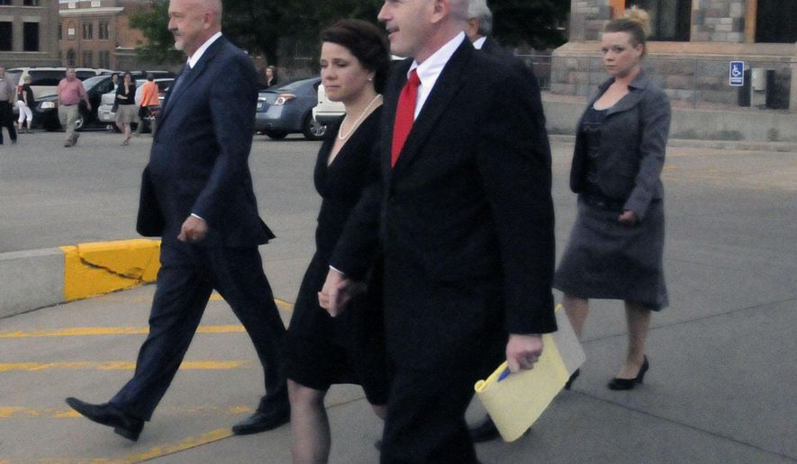 CORRECTS SOURCE - Former Republican U.S. Senate candidate Annette Bosworth, center, walks towards a vehicle from the Hughes County Courthouse in Pierre, S.D., on Wednesday, May 27, 2015, with her husband, Chad Haber, right, and her defense attorney, Dana Hanna, left. A South Dakota jury on Wednesday convicted former U.S. Senate candidate Annette Bosworth of election law violations. (AP Photo/James Nord)