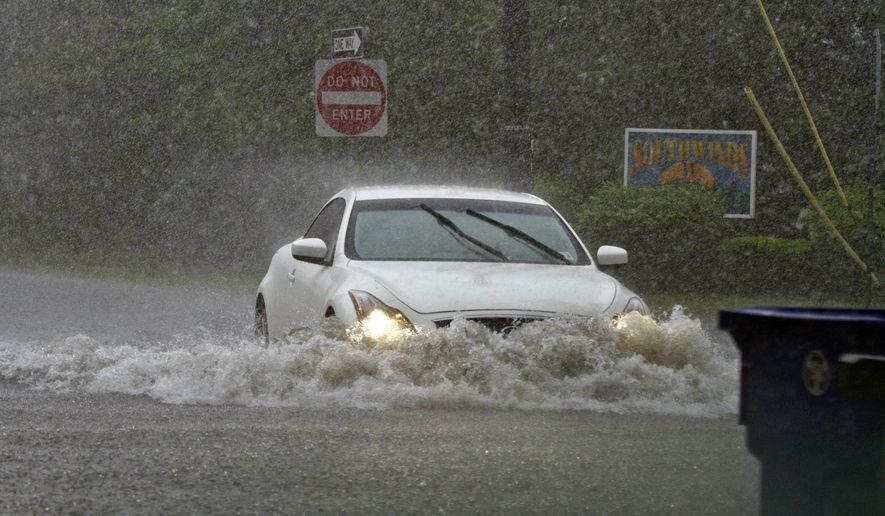 Vehicles drive through flash-flood water in Toms River, N.J., Thursday, May 28, 2015. Flash flood waters have begun receding in a coastal New Jersey town and there were no reports of injuries after people had to be rescued from flood waters.The Toms River police department said that fire and police units assisted people who were stuck in their cars in flood water. (Doug Hood/The Asbury Park Press via AP)  NO SALES