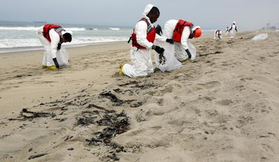 A cleanup crew collects balls of tar that washed ashore in Manhattan Beach, Calif. on Thursday, May 28, 2015. (AP Photo/Nick Ut)