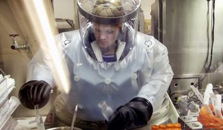 Microbiologist Ruth Bryan works with BG nerve agent simulant in Class III Glove Box in the Life Sciences Test Facility at Dugway Proving Ground, Utah, on May 11, 2003. The specialized airtight enclosure is also used for hands-on work with anthrax and other deadly agents. (Associated Press) **FILE**