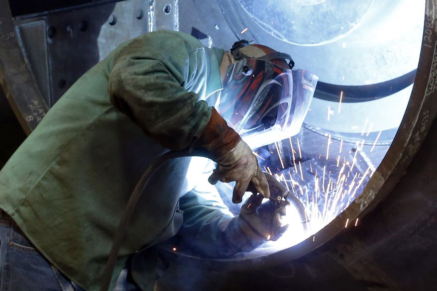 A man welds parts in fans for industrial ventilation systems at the Robinson Fans Inc. plant in Harmony, Pa., in this Thursday, Feb. 12, 2015, file photo. (AP Photo/Keith Srakocic)