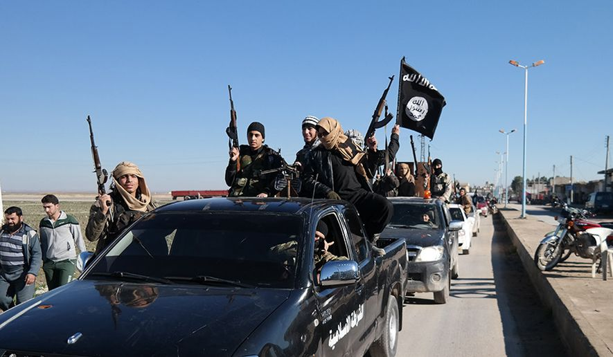 In this photo released on May 4, 2015, by a militant website, which has been verified and is consistent with other AP reporting, Islamic State militants pass by a convoy in Tel Abyad town, northeast Syria. (Militant website via AP)