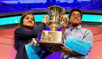 Vanya Shivashankar (left), 13, of Olathe, Kansas, and Gokul Venkatachalam, 14, of St. Louis, hold up the championship trophy as co-champions after winning the finals of the Scripps National Spelling Bee in Oxon Hill, Md., on May 28, 2015. (Associated Press)
