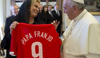 Pope Francis is presented with a Croatia national soccer team jersey reading his name in Croatian by Croatia's President Kolinda Grabar-Kitarovic, left, during a private audience in the pontiff's studio, at the Vatican, Thursday, May 28, 2015. (AP Photo/Andrew Medichini, Pool)