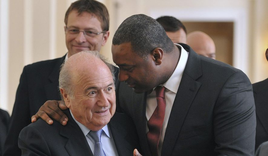 In this Wednesday, May 23, 2012, file photo the newly elected president of CONCACAF Jeffrey Webb talks to FIFA President Sepp Blatter, left, as they arrive at the meeting of the Confederation of North, Central American and Caribbean Association Football (CONCACAF), prior to the two-day congress of FIFA in Budapest, Hungary. Webb is among the soccer officials that were arrested and detained by Swiss police on Wednesday, May 27, 2015, at the request of U.S. authorities after a raid at Baur au Lac Hotel in Zurich. (Szilard Koszticsak/MTI via AP, File)