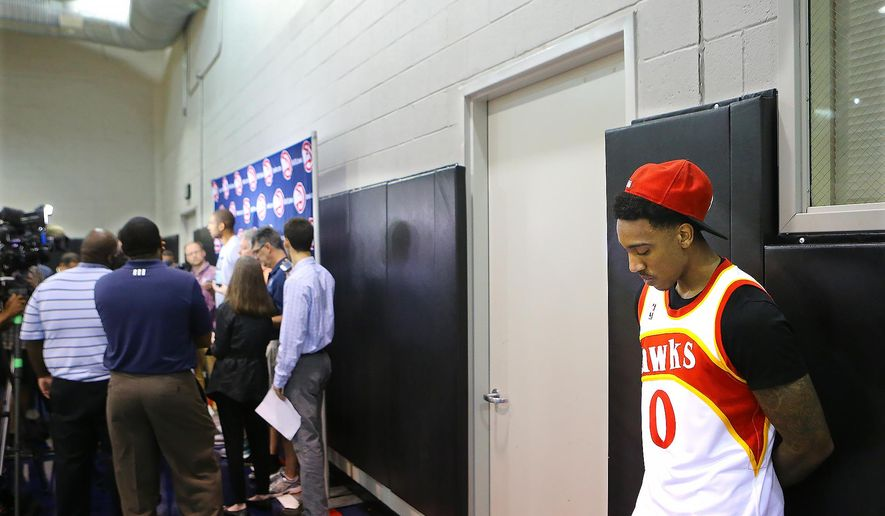 Atlanta Hawks' Jeff Teague waits in the wings for his team exit interview as Al Horford finishes his interview with the media  during an NBA basketball media availability, Thursday, May 28, 2015, in Atlanta.   (Curtis Compton/Atlanta Journal-Constitution via AP)  MARIETTA DAILY OUT; GWINNETT DAILY POST OUT; LOCAL TELEVISION OUT; WXIA-TV OUT; WGCL-TV OUT