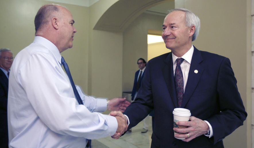 Rep. Joe Jett, D-Success, left, is greeted by Arkansas Gov. Asa Hutchinson before a meeting of the House Committee on State Agencies and Governmental Affairs at the Arkansas state Capitol in Little Rock, Ark., Thursday, May 28, 2015. (AP Photo/Danny Johnston)