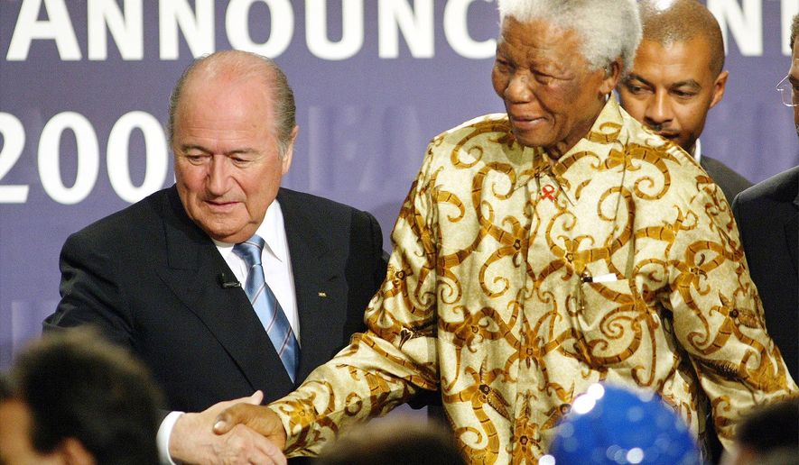 FILE - In this May 15, 2004 file photo, former South African President Nelson Mandela is assisted by FIFA president Sepp Blatter, left, in Zurich, Switzerland, where it was announced that South Africa would host the 2010 FIFA World Cup soccer tournament. The country's image has been shattered with allegations that its bid over a decade ago was involved in millions of dollars in bribes to secure FIFA votes and make sure of its historic place as Africa's first World Cup host. (AP Photo/Michael Probst, File)