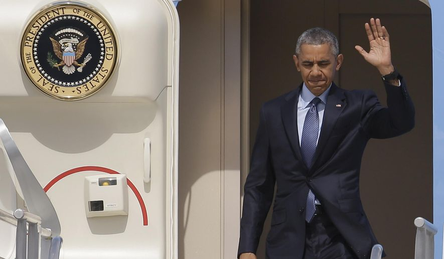 President Barack Obama waves as he disembarks from Air Force One at Miami International Airport, Wednesday, May 27, 2015, in Miami. The president is attending two Democratic National Committee fundraisers and the National Hurricane Center in this overnight visit. (AP Photo/Lynne Sladky)