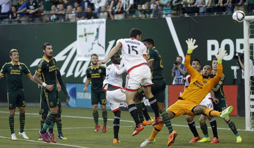 Portland Timbers goalkeeper Adam Kwarasey, right, dives as D.C. United defender Steven Birnbaum (15) heads the ball towards the goal on a corner kick during the first half of an MLS soccer game in Portland, Ore., Wednesday, May 27, 2015. Birnbaum did not score on this play.(AP Photo/Don Ryan)