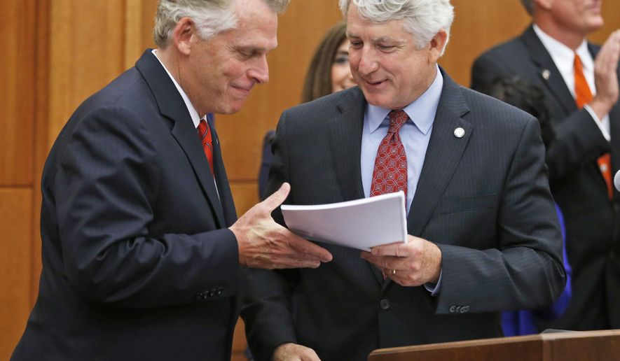 Virginia Attorney Gen. Mark Herring, right, gives a copy of the report by the Governors Task Force on Sexual Violence on college Campuses to Virginia Gov. Terry McAuliffe, left, during the final meeting of the group at the Capitol in Richmond, Va., Thursday, May 28, 2015.  The task force headed by Herring issued 21 recommendations to help combat sexual violence on college campuses.  (AP Photo/Steve Helber)