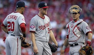 Washington Nationals starting pitcher Stephen Strasburg, center, stands on the mound alongside shortstop Ian Desmond (20) and catcher Wilson Ramos in the second inning of a baseball game against the Cincinnati Reds, Friday, May 29, 2015, in Cincinnati. (AP Photo/John Minchillo)