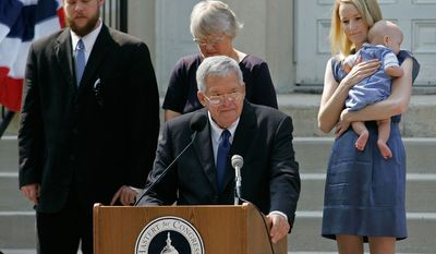 FILE - In this  Aug. 17, 2007, file photo, Rep. J. Dennis Hastert, front, R-Ill., announces that he will not seek reelection for a 12th term as he stands on the steps of the old Kendall County courthouse with, from left, his son Josh; wife Jean; and daughter-in-law Heidi, grandson Jack, in Yorkville, Ill. Federal prosecutors have indicted Thursday, May 28, 2015, the former U.S. House Speaker on bank-related charges. (AP Photo/Brian Kersey, File)