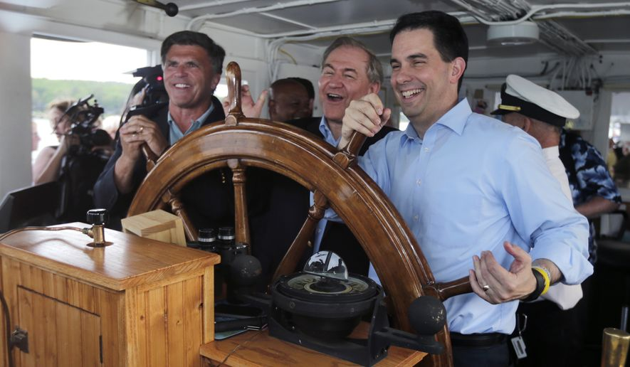 Wisconsin Gov. Scott Walker, right, takes the wheel with former Virginia Gov. Jim Gilmore, center, and former Maryland Gov. Bob Ehrlich during a fundraiser for the Belknap County Republican Committee aboard the motor vessel Mount Washington on Lake Winnipesaukee in New Hampshire, Friday, May 29, 2015. (AP Photo/Charles Krupa)