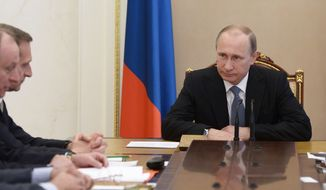 "Russian President Vladimir Putin chairs a meeting of the Security Council in the Kremlin in Moscow, Russia, Friday, May 29, 2015.  Russian President Vladimir Putin signed a decree on Thursday to make losses of Russian troops who are on ""special operations"" in peacetime,  a state secret. (Alexei Nikolsky/RIA-Novosti, Kremlin Pool Photo via AP)"