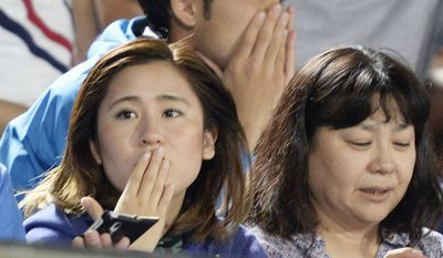 Japanese soccer fans react to a strong earthquake as they watch a J-League soccer match between the Shonan Bellmare and the Sanfrecce Hiroshima at BMW Stadium in Hiratsuka, southwest of Tokyo Saturday, May 30, 2015. (Associated Press) ** FILE **