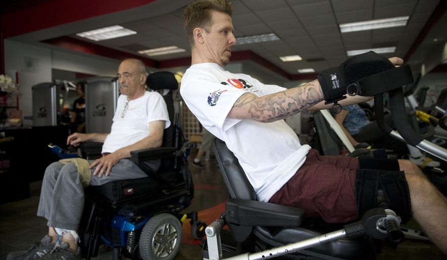 In this Tuesday, May 5, 2015 photo, Aaron Baker, right, a former motocross racer who was paralyzed from the neck down in a crash while practicing on a motocross track in 1999, exercises at the Center of Restorative Exercise in the Northridge section of Los Angeles. (AP Photo/Jae C. Hong)