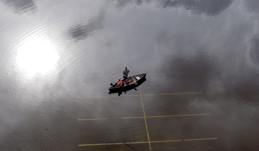 In this aerial photo, people prepare to launch a canoe from a flooded parking lot near Bear Creek Park Saturday, May 30, 2015, in Houston. The Colorado River in Wharton and the Brazos and San Jacinto rivers near Houston are the main focus of concern as floodwaters moved from North and Central Texas downstream toward the Gulf of Mexico. (AP Photo/David J. Phillip)