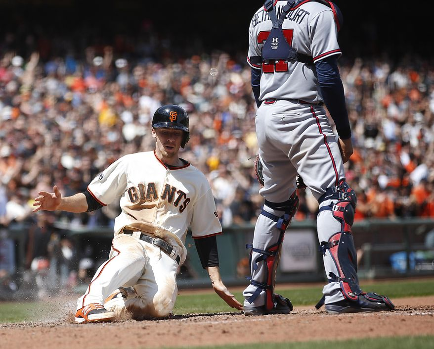 San Francisco Giants' Matt Duffy scores a run past Atlanta Braves catcher Christian Bethancourt (27) on a single by Gregor Blanco during the seventh inning of a baseball game, Sunday, May 31, 2015, in San Francisco. (AP Photo/Tony Avelar)