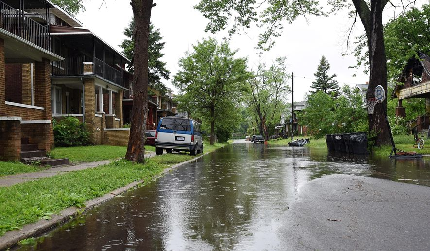 A puddle floods W. Savannah Street in Detroit on Sunday, May 31, 2015. Heavy rain has soaked parts of lower Michigan, causing flooding that closed part of one expressway for hours and dampened the excitement at the Detroit Grand Prix. (Robin Buckson/The Detroit News via AP) DETROIT FREE PRESS OUT - HUFFINGTON POST OUT - NO MAGS - NO SALES - MANDATORY CREDIT