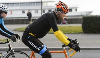In this March 16, 2015, file picture, U.S. Secretary of State John Kerry, rides a bike after a bilateral meeting with the  Iranian Foreign Minister in Lausanne, Switzerland. (Jean-Christophe Bott,Keystone via AP, file)