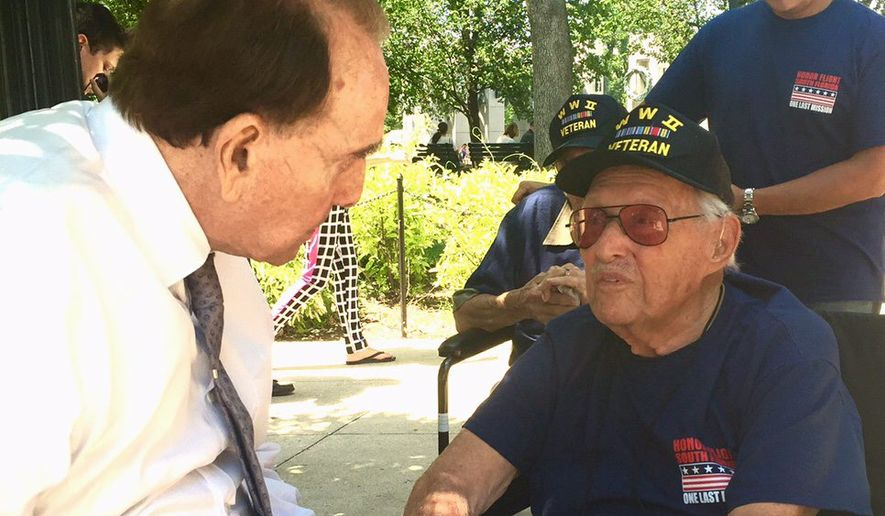 Former Sen. Bob Dole greeted veteran Philip Grayson of Miami at the National World War II Memorial. Mr. Dole is there nearly every Saturday. (Dave Boyer/The Washington Times)