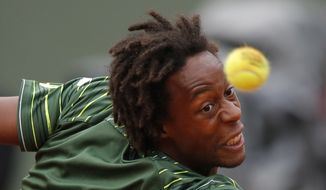 France's Gael Monfils returns the ball to Switzerland's Roger Federer during their fourth round match of the French Open tennis tournament at the Roland Garros stadium, Sunday, May 31, 2015 in Paris.  (AP Photo/Francois Mori)