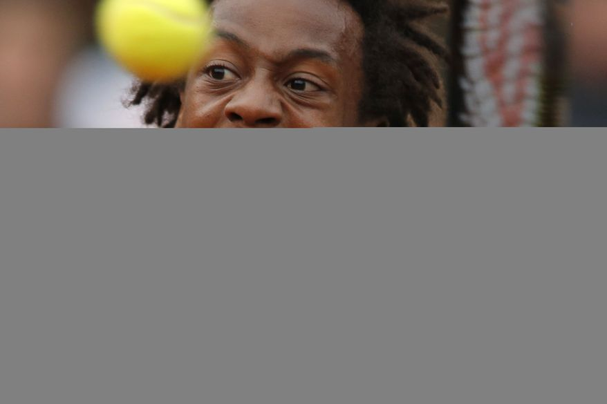 France's Gael Monfils plays a shot in his fourth round match of the French Open tennis tournament against Switzerland's Roger Federer at the Roland Garros stadium, in Paris, France, Sunday, May 31, 2015. (AP Photo/Francois Mori)