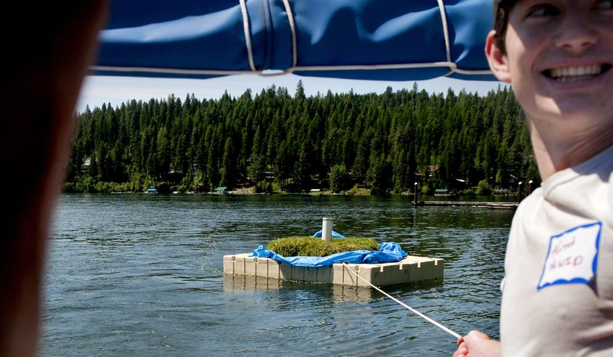 Forrest Walker of Hayden Lake Watershed Improvement District held onto the floating wetland as it was towed to a bay in the Northeast corner of Hayden Lake on Friday, May 29, 2015. Kootenai Environmental Alliance is launching 8 floating wetlands in bays around Hayden Lake this year. (Kathy Plonka/The Spokesman-Review via AP)
