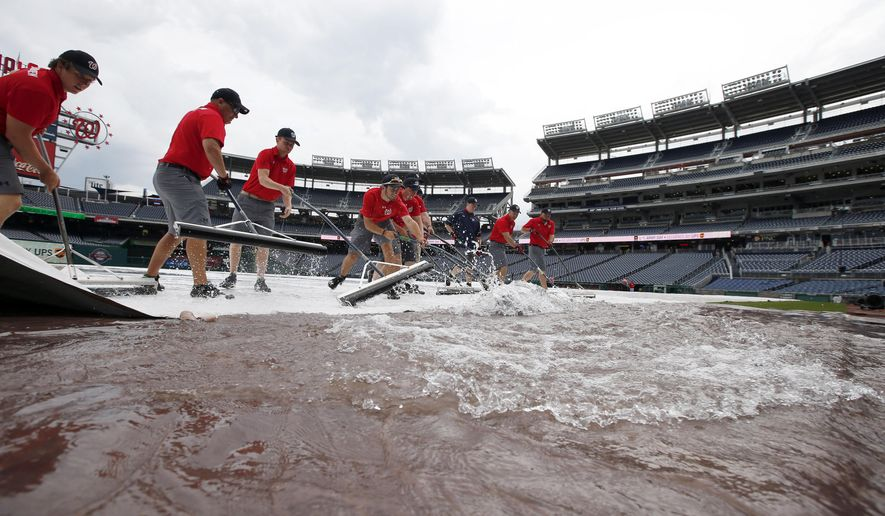 The Washington Nationals grounds crew squeegee's the tarp before an interleague baseball game between the Washington Nationals and the Toronto Blue Jays at Nationals Park, Monday, June 1, 2015, in Washington. (AP Photo/Alex Brandon)