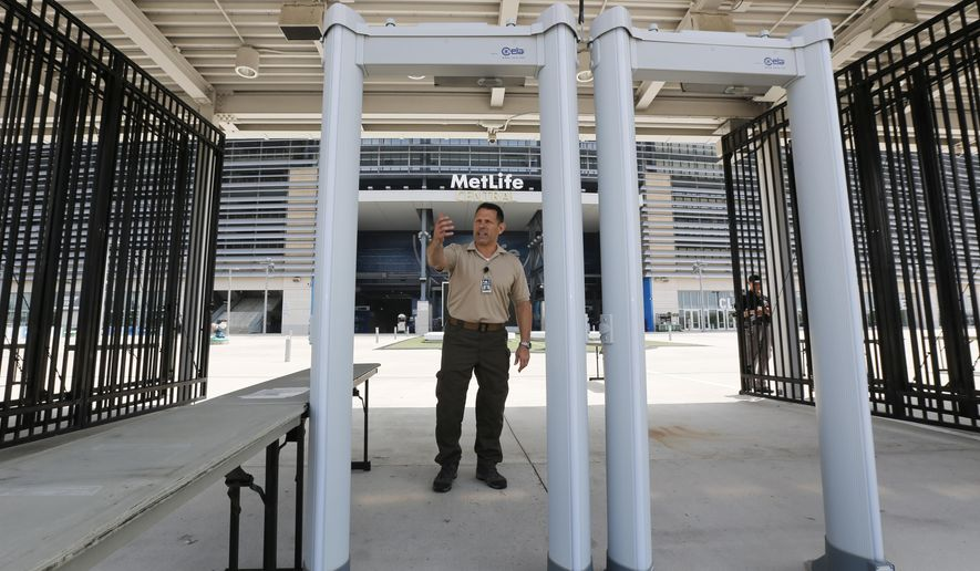 In this Thursday, May 28, 2015, photo, Danny DeLorenzi, director of security at MetLife Stadium, explains to The Associated Press the process for using metal detectors at a gate at the stadium in East Rutherford, N.J. Beginning June 1, the metal detectors will be used to screen people attending events at the stadium. (AP Photo/Julio Cortez)