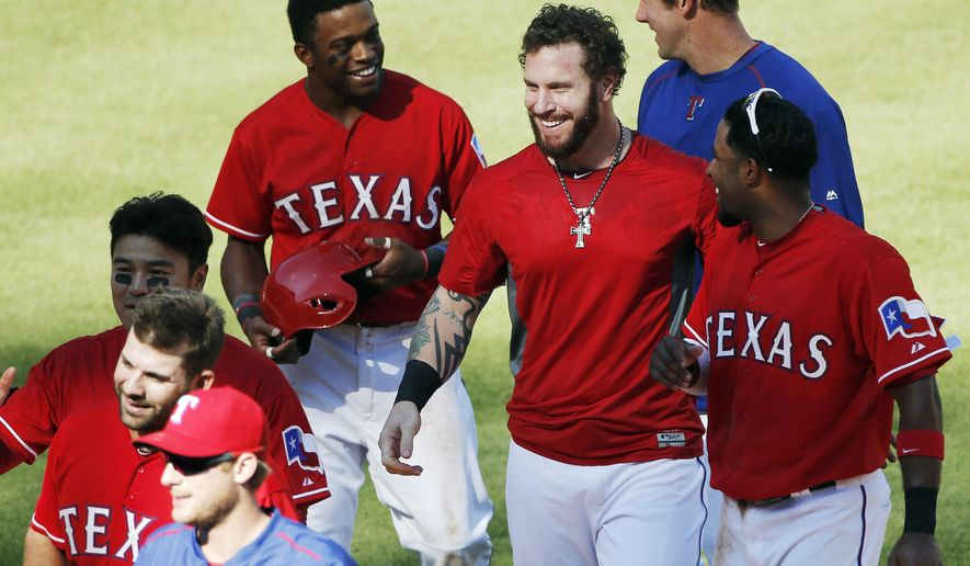 Texas Rangers Josh Hamilton, center, is congratulated by teammates after hitting a two-RBI walkoff double during the ninth inning of a baseball game against the Boston Red Sox, Sunday, May 31, 2015, in Arlington, Texas. Texas won 4-3. (AP Photo/Brandon Wade)