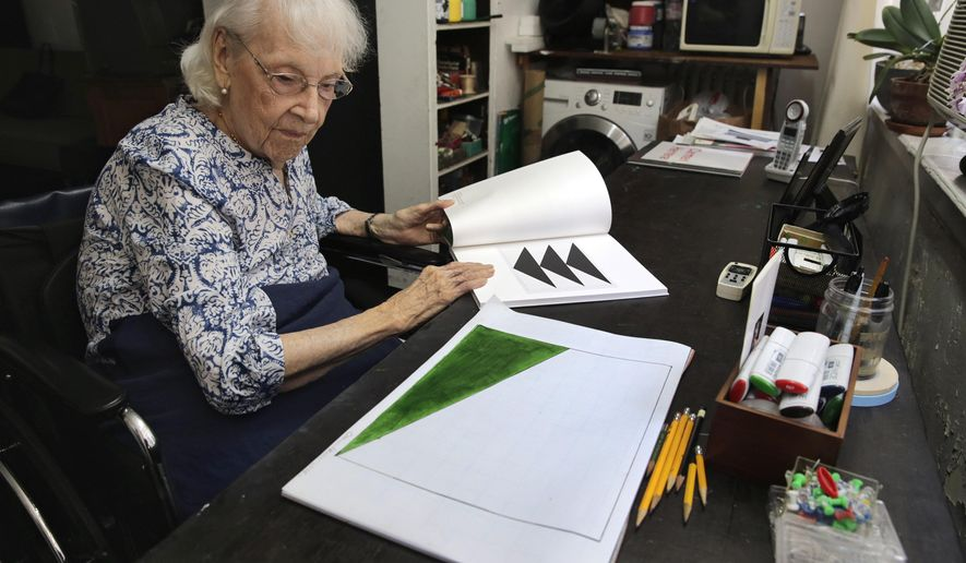 In this Friday, May 29, 2015 photo, artist Carmen Herrera looks at a sketch for one of her paintings as she leafs through a gallery catalogue of some of her work, in her New York studio. Herrera, who turned 100 on Sunday, May 31, says she's still bursting with ideas she wants to put on canvas. (AP Photo/Richard Drew)