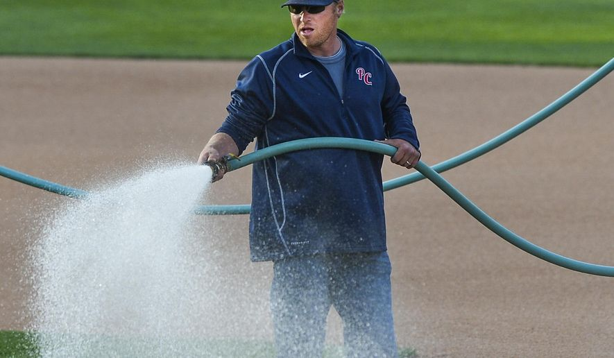 In this April 21, 2015 photo, Peoria Chiefs groundskeeper Mike Reno waters the infield before a game at Dozer Park in Peoria, Ill. Reno is an artist, from painting an end zone every year at the Super Bowl, to carefully manicuring Dozer Park nightly for Peoria Chiefs games. Fitting, for a guy who graduated with a degree in sculpture from Arizona State University. (Ron Johnson/Journal Star via AP)