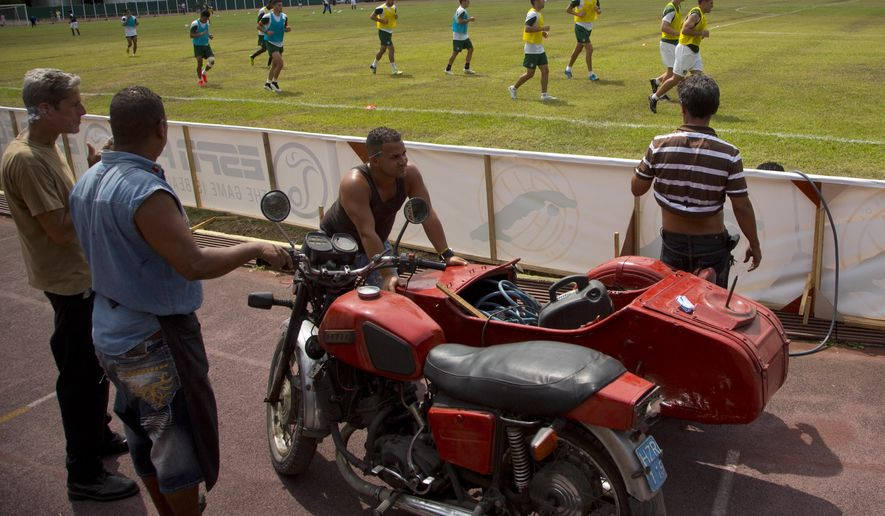 Stadium workers use an old Russian motorcycle with a sidecar, which they use to transport tools at the Pedro Marrero stadium, as New York Cosmos soccer players train for a friendly against Cuba's national team, in Havana, Cuba, Monday, June 1, 2015. On Tuesday, the team will become the first U.S. professional team to play in Cuba since Presidents Raul Castro and Barack Obama announced that they were re-establishing diplomatic relations. (AP Photo/Ramon Espinosa)