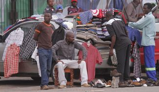 Many Zimbabweans turn their cars into makeshift secondhand clothing stores to beat unemployment, but reliance on Western providers leaves African industries struggling with slowed development. (Associated Press)