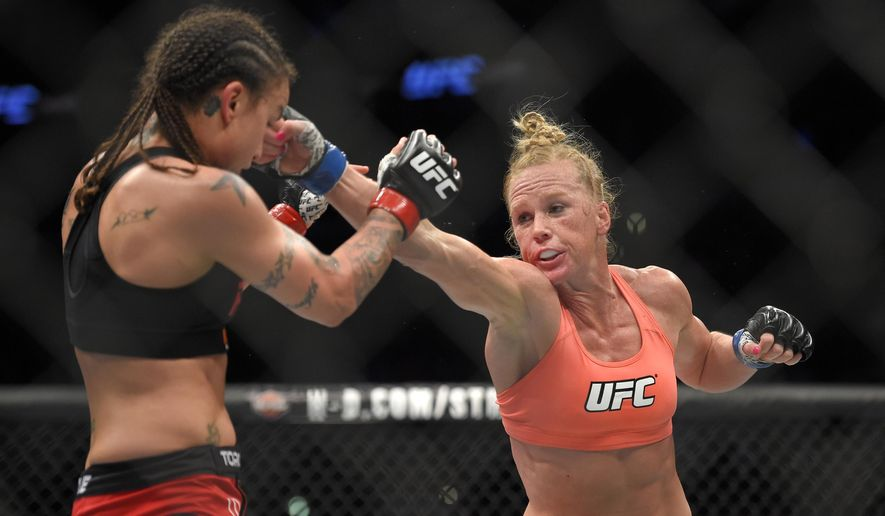 "FILE - This Feb. 28, 2015 file photo shows Holly Holm, right, connects with Raquel Pennington during a UFC 184 mixed martial arts bantamweight bout in Los Angeles.  Holm, the world's former No. 1-rated female boxer-turned-mix martial arts fighter, is headed to the big screen. She is scheduled to appear with fellow Ultimate Fighting Championship fighter and Tacoma, Washington native Miesha Tate in an upcoming film called ""Fight Valley."" (AP Photo/Mark J. Terrill,File)"