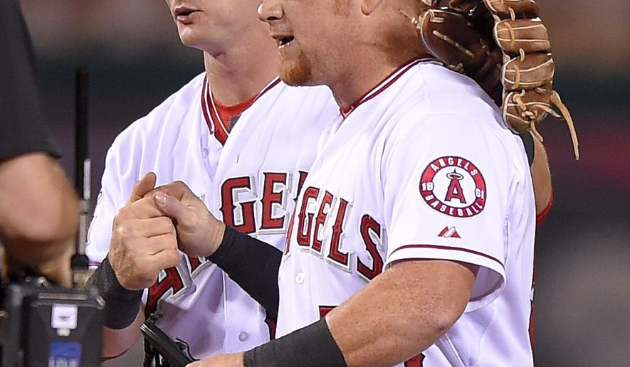 Los Angeles Angels' Johnny Giavotella, left, and Kole Calhoun congratulate each other after the Angels defeated the Detroit Tigers 4-2 in a baseball game, Sunday, May 31, 2015, in Anaheim, Calif. (AP Photo/Mark J. Terrill)