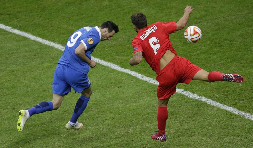 Dnipro's Nikola Kalinic, left, heads the ball to score against Sevilla's Daniel Carrico during the final of the soccer Europa League between FC Dnipro Dnipropetrovsk and Sevilla FC at the National Stadium in Warsaw, Poland, Wednesday, May 27, 2015. (AP Photo/Michael Sohn)