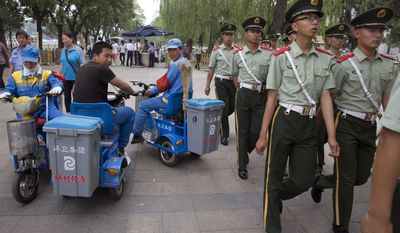 Chinese paramilitary policemen march past street cleaners near Tiananmen Square in Beijing Monday, June 1, 2015. The Chinese capital maintains a tight security around Tiananmen Square ahead of the 26th anniversary of China's June 4 bloody crackdown on pro democracy demonstrators. (AP Photo/Ng Han Guan)
