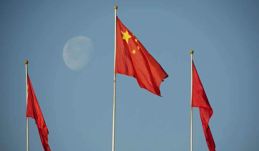 The moon sets over flags atop the Great Hall of the People in Beijing. (Associated Press)