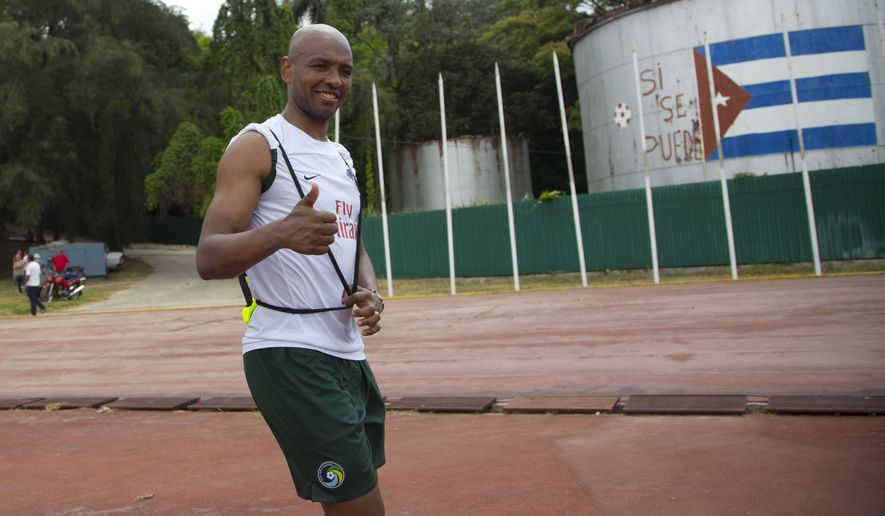 Brazilian-born Cosmos soccer player Marcos Senna gives a thumbs up to journalists as he arrives to train at the Pedro Marrero stadium in Havana, Cuba, Monday, June 1, 2015. Cuban officials said the upcoming friendly match between New York Cosmos team and Cuba's national team was a sign of soccer's growing popularity on the island, and an important step in the normalization of the relationship between the U.S. and Cuba. (AP Photo/Ramon Espinosa)
