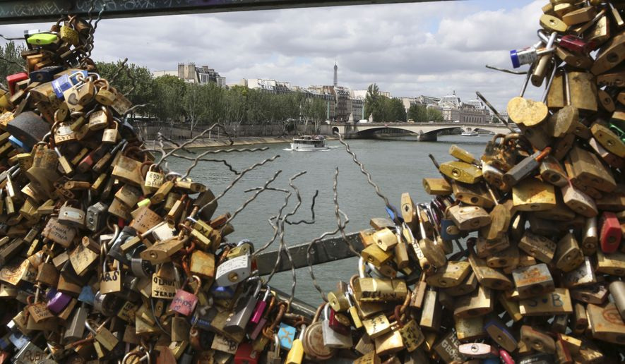 The Eiffel tower appears through the partly lock-free railing of the famed Pont des Arts bridge in Paris, Monday June 1, 2015. Lovers in Paris, beware: City authorities are taking down thousands of padlocks affixed to the famed Pont des Arts bridge. (AP Photo/Remy de la Mauviniere)