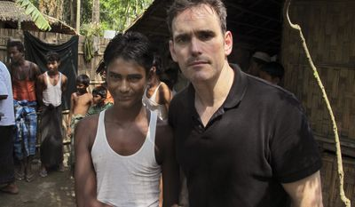 In this Friday, May 29, 2015 photo, American actor Matt Dillon, right, shakes hands with Noor Alam, a 17-year old Rohingya survivor of human-trafficking at Thetkabyin village, north of Sittwe in the western state of Rakhine, Myanmar. Dillon puts a rare celebrity spotlight on the plight of Myanmar's long-persecuted Rohingya Muslims, visiting a hot, squalid camp for tens of thousands displaced by violence and a port that has served as one of the main launching pads for their exodus by sea. (AP Photo/Robin McDowell)