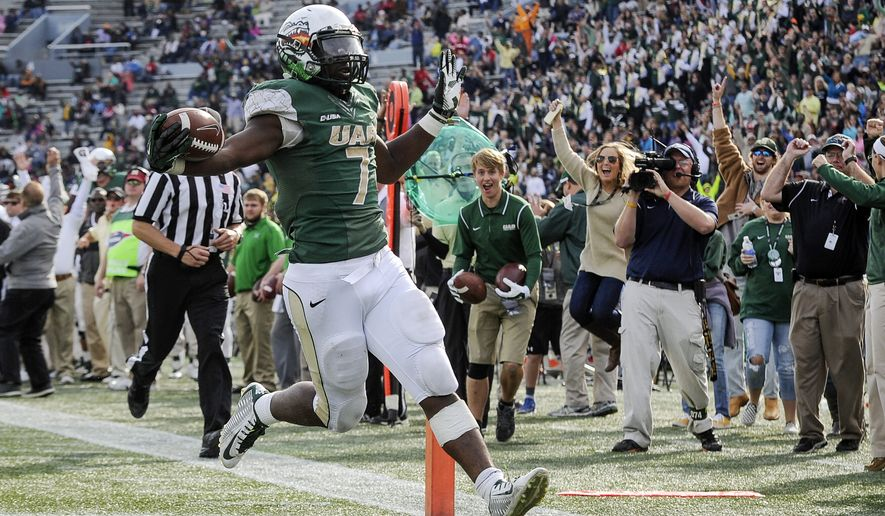 File - In this Saturday, Nov. 22, 2014, file photo, UAB running back Jordan Howard (7) scores a touchdown against Marshall during the fourth quarter of an NCAA college football game, in Birmingham, Ala. UAB president Ray Watts is bringing the football program back. He told The Associated Press that he decided on Monday, June 1, 2015 to reverse the earlier decision after meetings with UAB supporters continued through the weekend. He says donors have pledged to make up the estimated $17.2 million deficit over the next five years if football is restored. (AP Photo/John Amis, file)