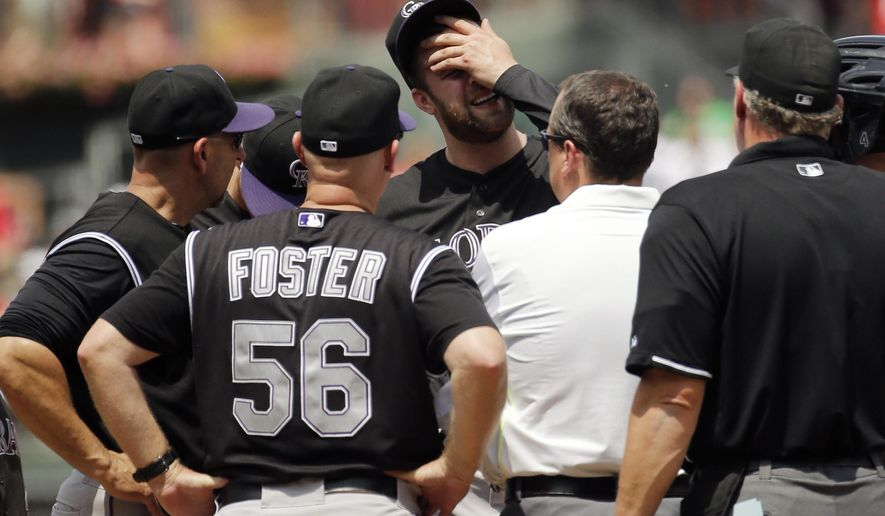 Colorado Rockies starting pitcher Jordan Lyles wipes his face as he talks with team personnel after suffering an injury during the second inning of a baseball game against the Philadelphia Phillies, Sunday, May 31, 2015, in Philadelphia. Lyles was pulled from the game. Colorado won 4-1. (AP Photo/Matt Slocum)