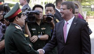 U.S. Defense Secretary Ash Carter, right, shakes hands with his Vietnamese counterpart Gen. Phung Quang Thanh before their talks behind closed doors in Hanoi, Vietnam Monday, June 1, 2015. Carter is on a three-day visit to Vietnam to deepen military cooperation between the two former foes. (AP Photo/Tran Van Minh.)